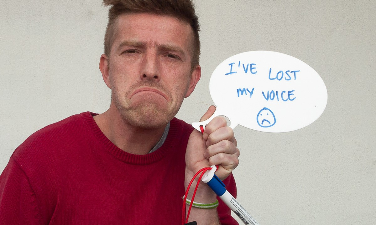 Lost Voice Whiteboard - A friend poses with a sad face and holds the whiteboard speech bubble with the message 'I've lost my voice'
